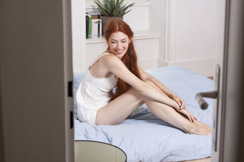 Sleepy young woman sitting on her bed in the morning - JUNF000061