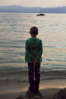 Italy, Lake Garda, boy looking at sunset - SARF000841