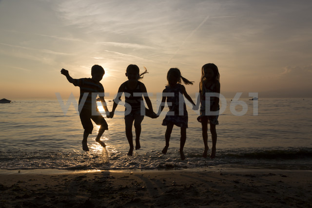 Italy, Lake Garda, children jumping on beach at sunset - SARF000842