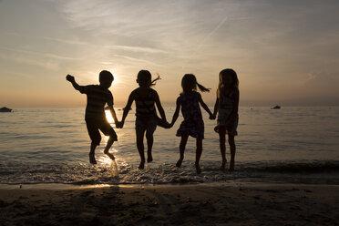 Italy, Lake Garda, children jumping on beach at sunset - SARF000842
