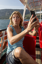 Italy, Lake Garda, woman taking selfie on tourboat - SARF000830