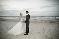 Germany, Mecklenburg-Western Pomerania, Ruegen, Sellin, bridal couple standing hand in hand on the beach - MABF000248