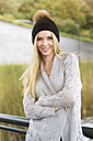 Portrait of smiling young woman wearing bobble hat and cardigan - GDF000448