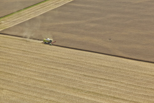 Germany, Bavaria, aerial view of combine harvester on cornfield - KDF000033
