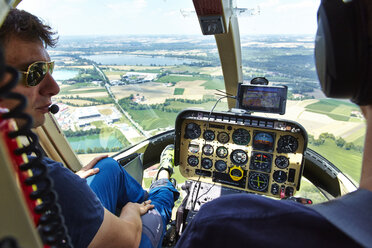 Germany, Bavaria, pilot and copilot in cockpit of a helicopter - KD000034