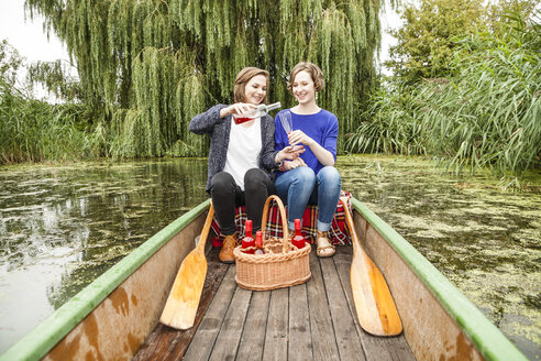 Two young woman in rowing boat with bottle and glass - DISF001029