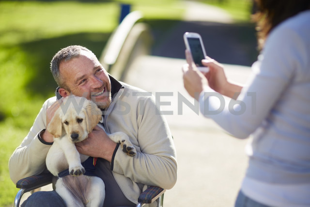 Woman taking picture of man with dog puppy in wheelchair - ZEF000398