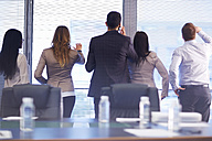 Group of businesspeople looking through sunblinds in boardroom - ZEF000281