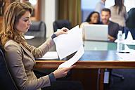 Businesswoman reading document in boardroom - ZEF000874
