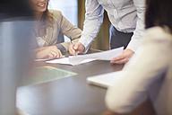 Businessman signing document in boardroom - ZEF000878
