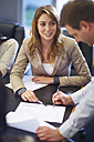 Businessman signing document in boardroom - ZEF000298