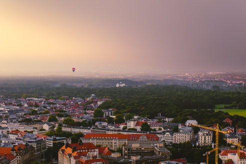 Germany, Saxony, Leipzig, hot air balloon hovering over the city at evening twilight - ZMF000340