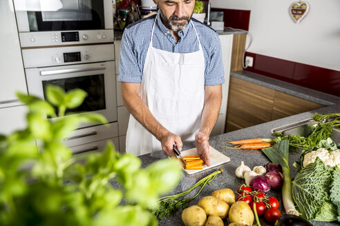 Austria, Man in kitchen chopping carrots - MBEF001247