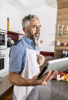 Austria, Man in kitchen holding digital tablet, looking for recipe - MBEF001259