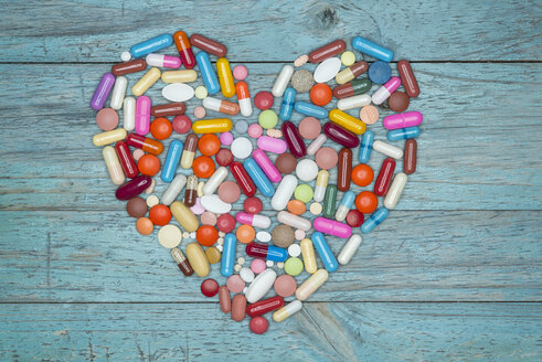 Tablets, pills and capsules shaped like a heart on blue wood - OPF000001