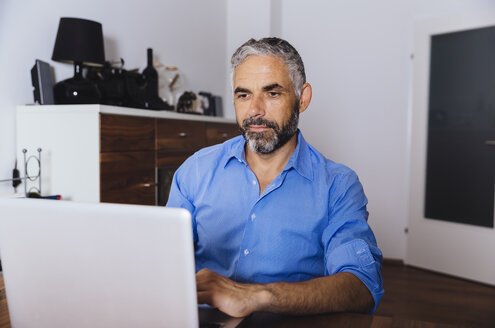 Portrait of businessman working with laptop at home office - MBEF001181