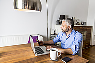 Portrait of businessman working with laptop at home office - MBEF001308