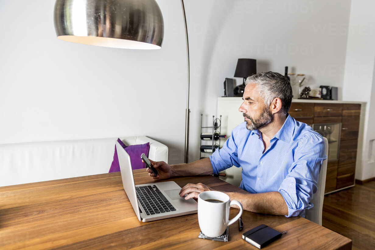 Portrait of businessman working with laptop at home office - MBEF001308 - Martin Benik/Westend61