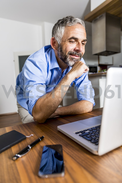 Portrait of smiling businessman at home office looking at his laptop - MBEF001297 - Martin Benik/Westend61