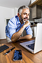 Portrait of smiling businessman at home office looking at his laptop - MBEF001297