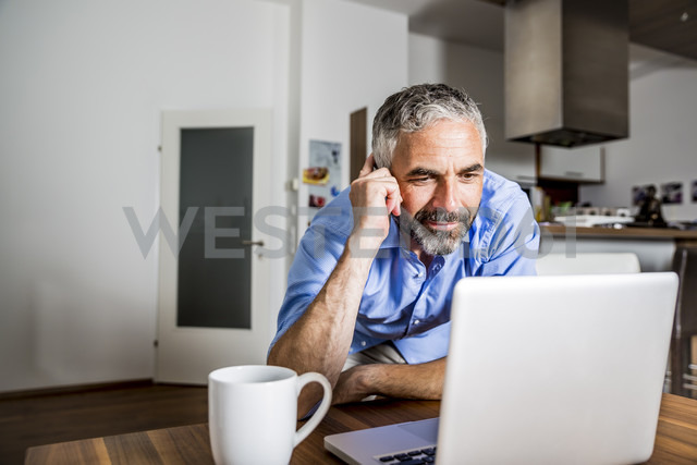 Businessman looking at his laptop - MBEF001299