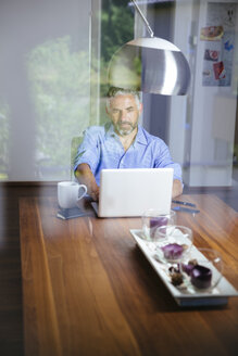 Businessman working with laptop at home office - MBEF001184