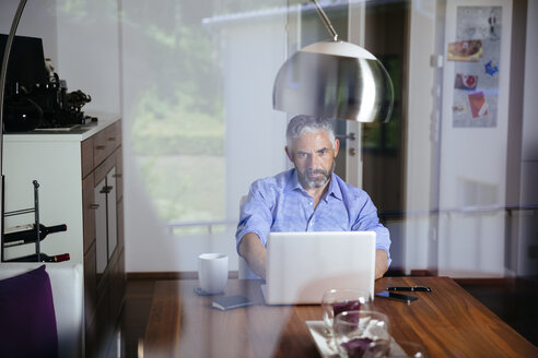 Businessman working with laptop at home office - MBEF001187