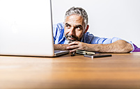 Portrait of businessman with laptop at home office - MBEF001305