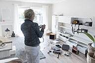 Woman photographing chaos after burglary when coming back in her one-family house - ONF000611