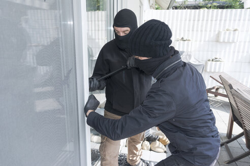 Two burglars opening terrace door of an one-family house with hammer and crowbar at daytime - ONF000623