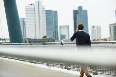 Germany, Hesse, Frankfurt, young businessman walking on a bridge telephoning with his smartphone - UUF001819