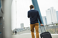 Germany, Hesse, Frankfurt, young businessman walking on a bridge telephoning with his smartphone - UUF001823