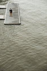 Germany, Hesse, Frankfurt, young man standing on a jetty with his digital tablet - UUF001827