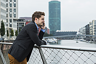 Germany, Hesse, Frankfurt, young businessman standing on a bridge telephoning with his smartphone - UUF001831