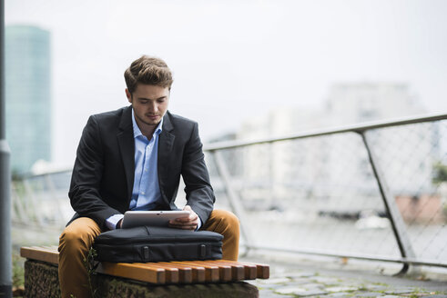 Germany, Hesse, Frankfurt, young man sitting on a bench using his digital tablet - UUF001888