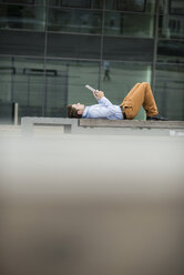 Germany, Hesse, Frankfurt, young man lying on back using his digital tablet - UUF001847