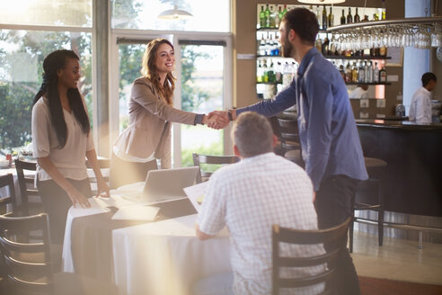 Two people greeting each other at a business meeting in a restaurant - ZEF001008