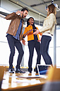Three happy creative people dancing on a conference table - ZEF000912