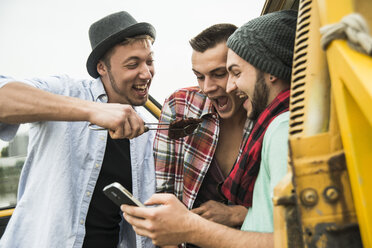 Group of friends with cell phone and steak at a car - UUF001875