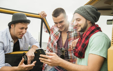 Group of friends with cell phone at a car - UUF001876