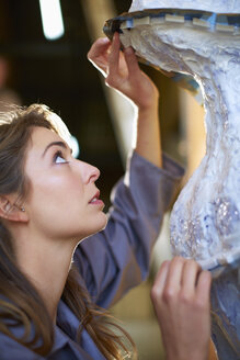 South Africa, Cape Town, Young preparing rubber mold for bronze sculpture - ZEF000334