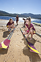 Four female rowers placing oars at lakeshore - ZEF000933