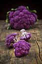 Whole purple cauliflower and cauliflower florets on wood - LVF001894