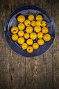 Dish of yellow cherry tomatoes on dark wood - LVF001899