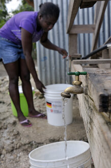 Haiti, Petit Goave, Woman getting clean water from treatment plant - FLK000436