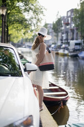 Netherlands, Amsterdam, young woman standing besides a car in front of a town canal - NNF000022