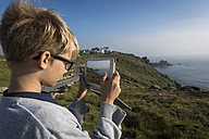 UK, Cornwall, boy photographing landscape at Land's End with his digital tablet - PAF000970