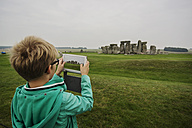 UK, Wiltshire, boy photographing Stonehenge with his digital tablet - PAF000956