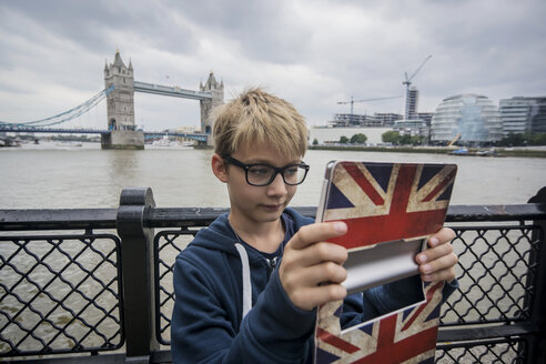 UK, London, boy taking picture with digital tablet at Tower Bridge - PAF000976