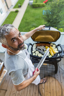 Man barbecuing on his balcony - MBEF001273